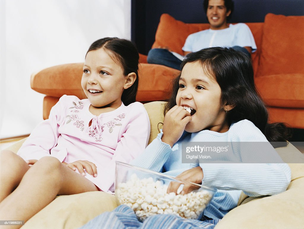 Two Young Sisters Sitting at Home Eating Popcorn, Their Dad in the Background : Stock Photo