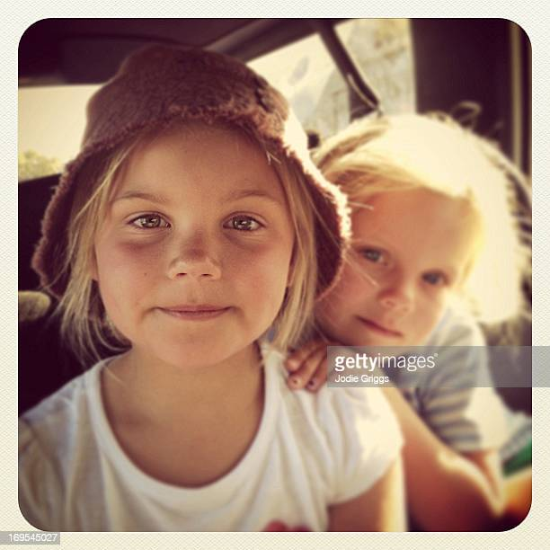 Two young sisters sitting in the back of a car