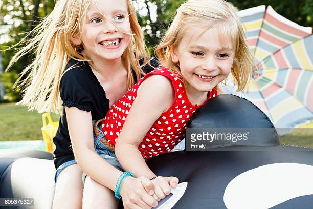 Two young sisters sitting on inflatable whale in park