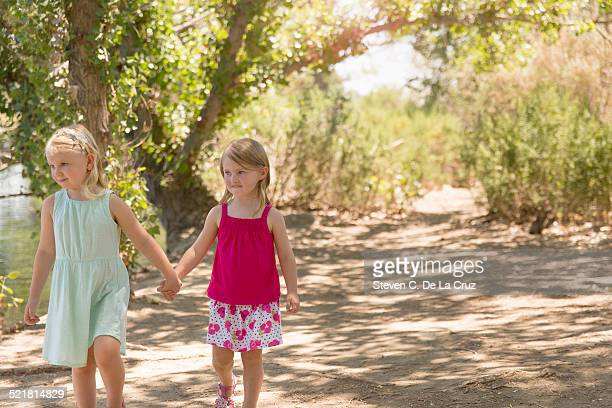 Two young sisters strolling and holding hands on riverbank