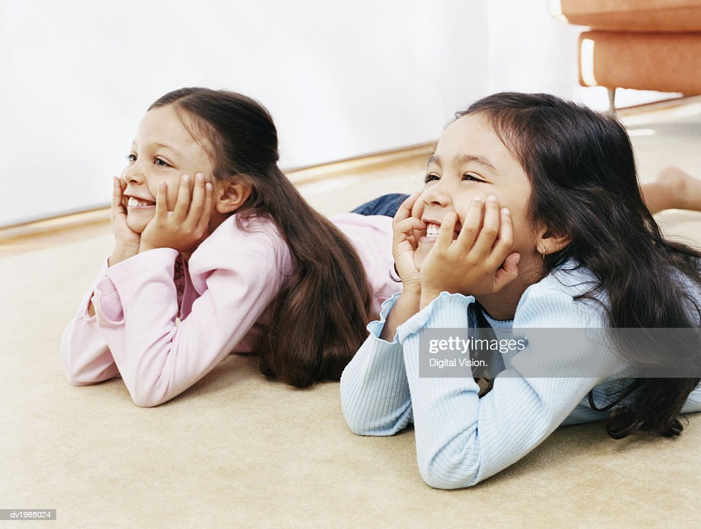 Two Young Sisters Watching TV Lying on the Living Room Floor : Stock Photo
