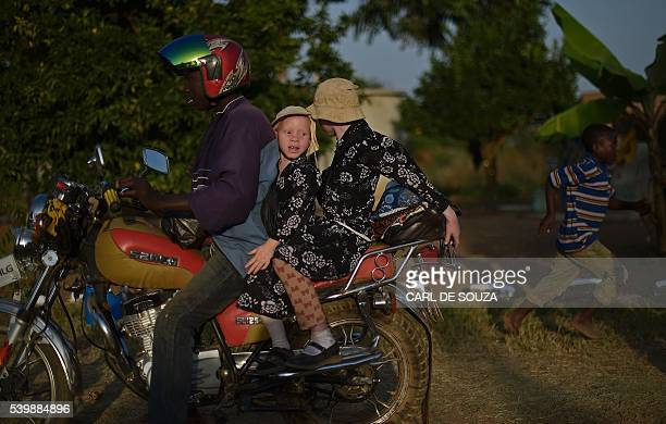 Two young sisters with albinism sit on a motorbike during International Albinism Awareness day on Ukerewe Island on Lake Victoria on June 13 2016...