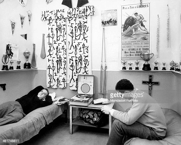 Two young Spanish men relaxing in a bedroom A poster of the Plaza de Toros of Linares hanging on the wall Madrid 1960