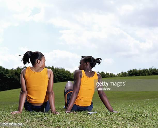 Two young sportswomen sitting in field, rear view