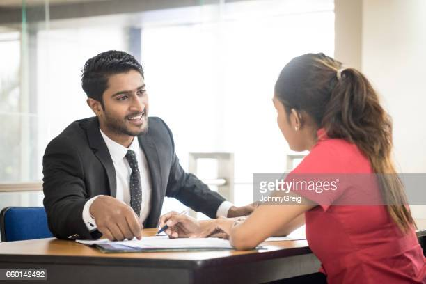 Two young Sri Lankan business colleagues in modern office