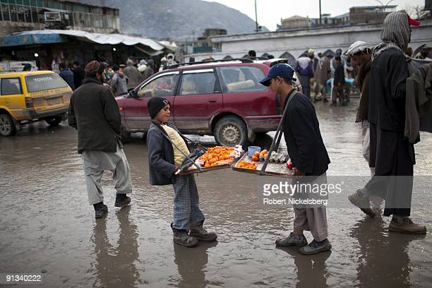 Two young street vendors selling deep fried hard boiled eggs April 6 2009 compare trays in the downtown market district Kabul Afghanistan Kabul has...