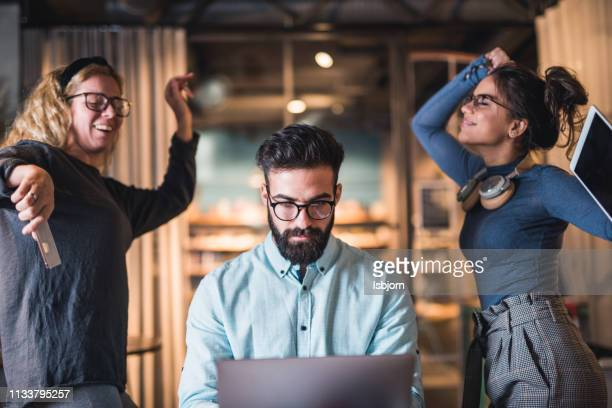 two young students dancing while man student training to work at laptop. - education building stock pictures, royalty-free photos & images
