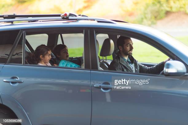 two young students getting picked up from school - sollevare foto e immagini stock