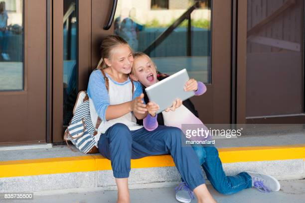 Two young students girls back to school m on making selfie gital tablet at the entrance of the school