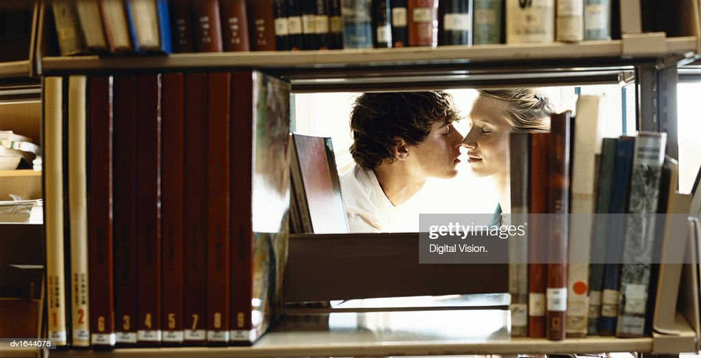 Two Young Students Kissing in a Library, Viewed Through a Gap Between Books on a Shelf : Stock Photo