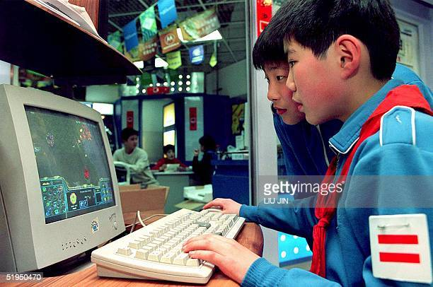 Two young students play a popular adventure game at a computer store after their classes in Shanghai 14 March 2000 As incomes rise throughout China's...