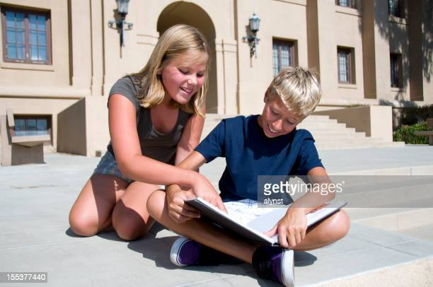 Two Young Students Reading School Book