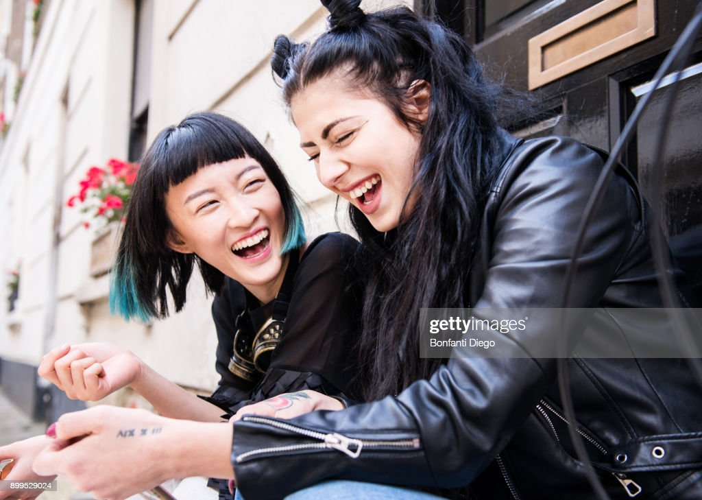 Two young stylish female friends sitting doorstep laughing : Stock Photo