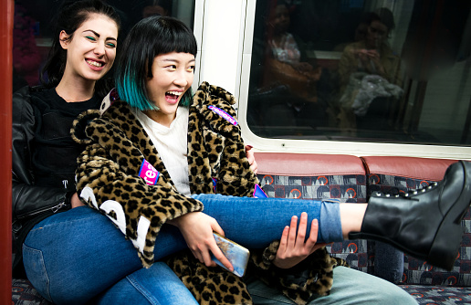 Two young stylish women laughing on underground train carriage - gettyimageskorea
