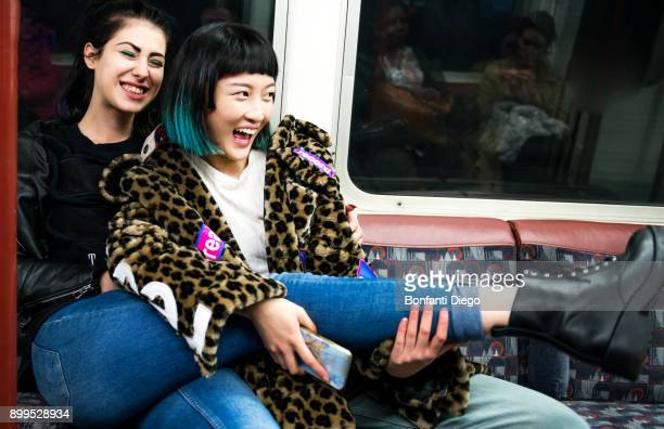 two young stylish women laughing on underground train carriage - 地下鉄 ストックフォトと画像