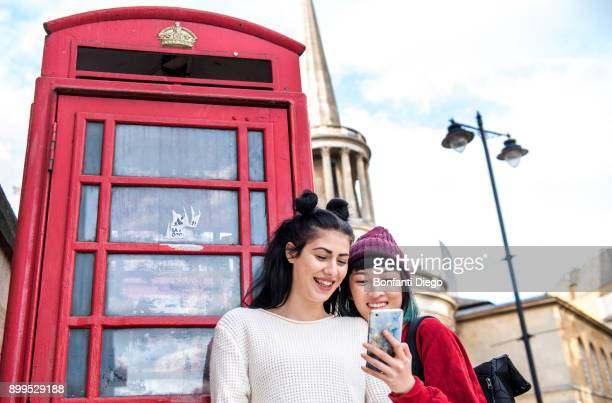 two young stylish women looking at smartphone by red phone box, london, uk - red telephone box stock pictures, royalty-free photos & images
