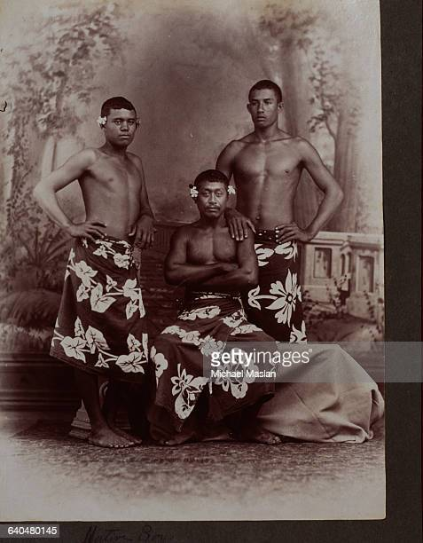 Two young Tahitian men stand and an older man sits for a portrait in front of a painted backdrop They are all wearing printed sarongs around their...
