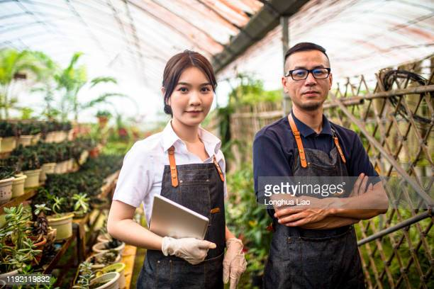 two young technicians are in the flower bed - botanist stock pictures, royalty-free photos & images