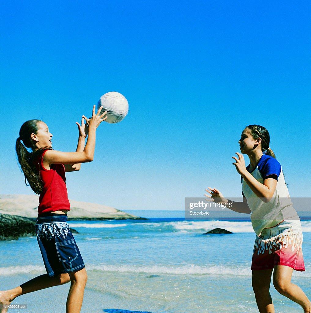 Preteen Girls Playing Beach Volleyball Foto de stock
