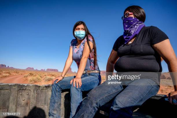 two young teenage navajo sisters riding in the bed of a pickup wearing covid-19 masks to flatten the curve and stop the spread of the corona virus - cherokee indian women stock pictures, royalty-free photos & images