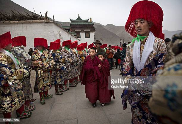 Two young Tibetan Buddhist monks of the Gelug or Yellow Hat order walk passed men in traditional clothing before a procession during Monlam or the...