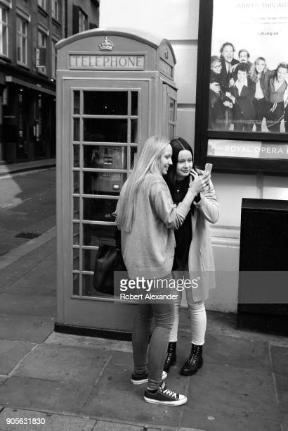 Two young tourists review souvenir smartphone photographs of themselves taken as each posed inside an iconic red British telephone booth in the...