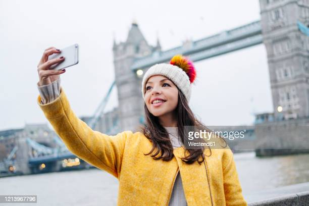 two young tourists sitting on wall, using smartphone, with  london bridge in background - photographing stock pictures, royalty-free photos & images
