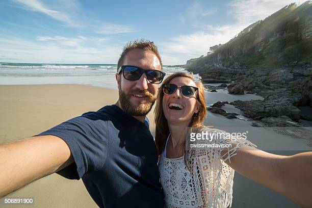 Two young travelers on the beach taking selfie portrait