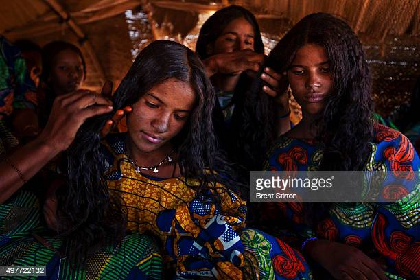 Two young Tuareg women have their hair dressed by other Tuareg women inside a traditional nomad tent at a Tuareg Nomad camp on October 11 2009 in...