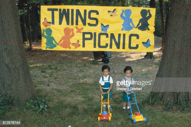 Two young twin boys push plastic toy lawn mowers over the grass between two large trees in a park A large yellow banner over their heads reads 'Twins...