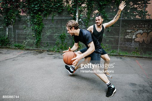 Two Young Urban Basketball Players Battling For Control Of The Ball