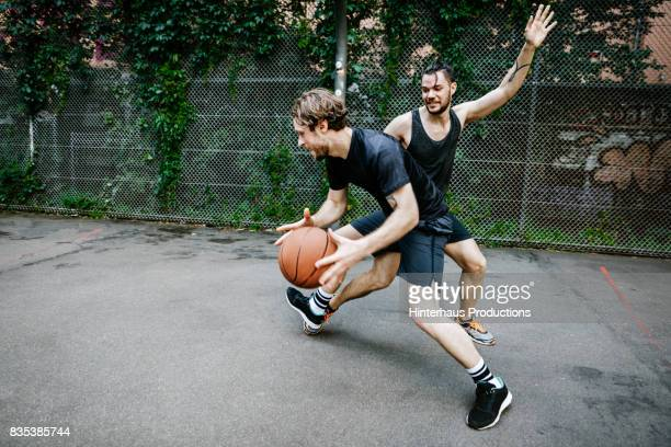 two young urban basketball players battling for control of the ball - basketball sport stock pictures, royalty-free photos & images