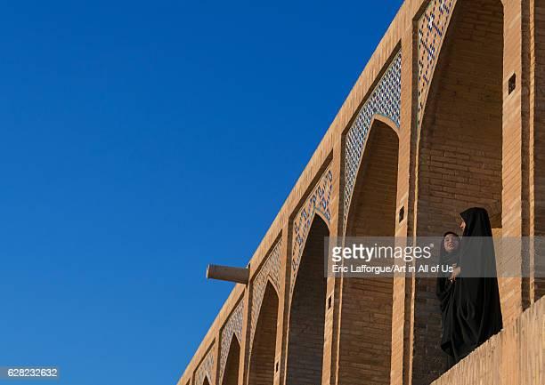 Two young veiled women on Khaju bridge Pol-e Khaju, Isfahan Province, Isfahan, Iran on October 13, 2016 in Isfahan, Iran.