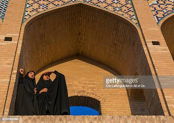 Two young veiled women on Khaju bridge Pol-e Khaju looking away, Isfahan Province, Isfahan, Iran on October 13, 2016 in Isfahan, Iran.