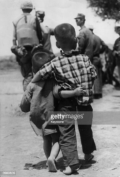 Two young Vietnamese children arminarm behind a group of US marines