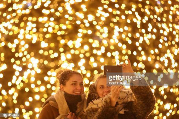 Two young visitors from Mozambique and Ireland shoot a selfie in front of a giant Christmas tree at the annual Christmas market at Alexanderplatz on...