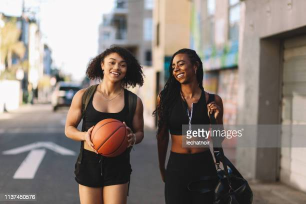 two young walking home  after playing basketball in la, california - 20 24 years stock pictures, royalty-free photos & images