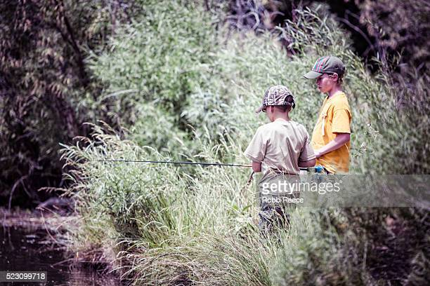 two young, weblo boy scouts fishing together near their camp in colorado. - robb reece stock-fotos und bilder