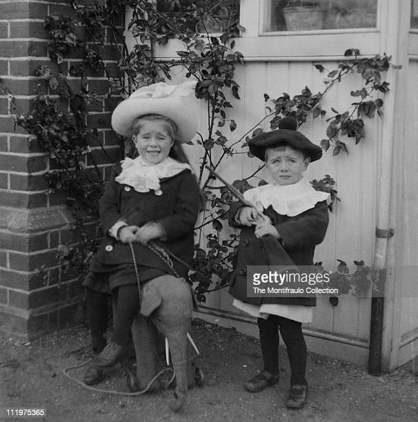 Two young well dressed children posing outside a house the young boy holds a toy rifle whilst the girl sits on a Stiefftype pushalong toy elephant...