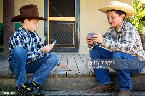 Two young western brothers playing cards on porch