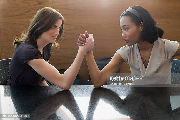 two young woman arm wrestling - female wrestling holds stockfoto's en -beelden