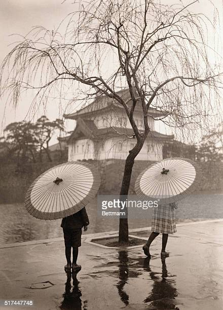 Two young woman carrying Japanese umbrellas walk along the moatside of the Imperial Palace in Tokyo on a rainy day