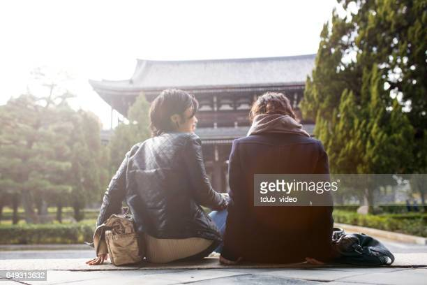 Two young woman chatting at a temple in Kyoto, Japan