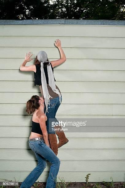 Two Young Woman Climbing Wall