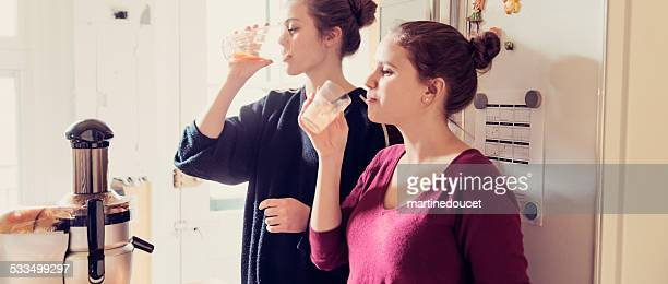 Due giovane donna bere succhi freschi, con Spremiagrumi in cucina