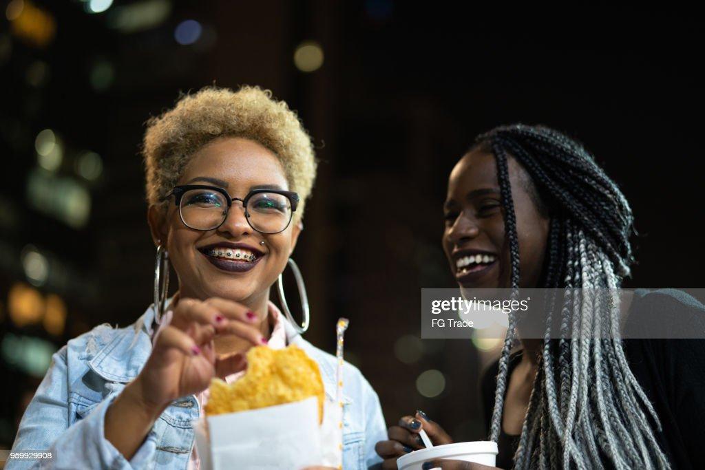 Zwei junge Frau Essen Pastell auf der Straße nach der Arbeit : Stock-Foto