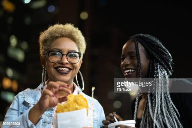dois jovem comendo pastel na rua depois do trabalho - colorido pastel - fotografias e filmes do acervo
