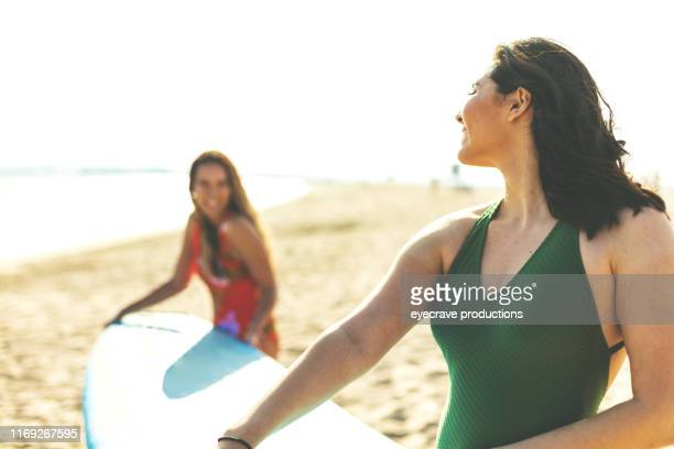 Two young woman enjoying Seal Beach in California on the edge of the ocean near the waves and water carrying a surfboard