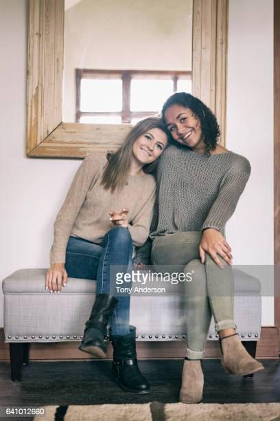 two young woman friends laughing together indoors - côte à côte photos et images de collection