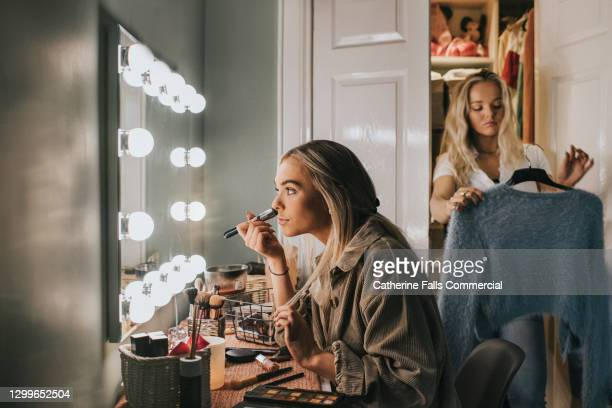 two young woman getting ready - one puts on foundation and the other decides what outfit to wear - 20 24 years stock pictures, royalty-free photos & images